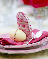A close up of an Easter place setting of a decorated egg on pink and white china