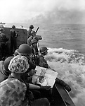 Marines aboard a Higgins boat get a last look at beauty as they move toward the smoke-covered island of Tarawa where battle was awaiting.
