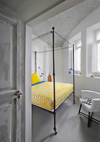 An antique iron four-poster bed is teamed with an armchair by Paola Navone in the bedroom