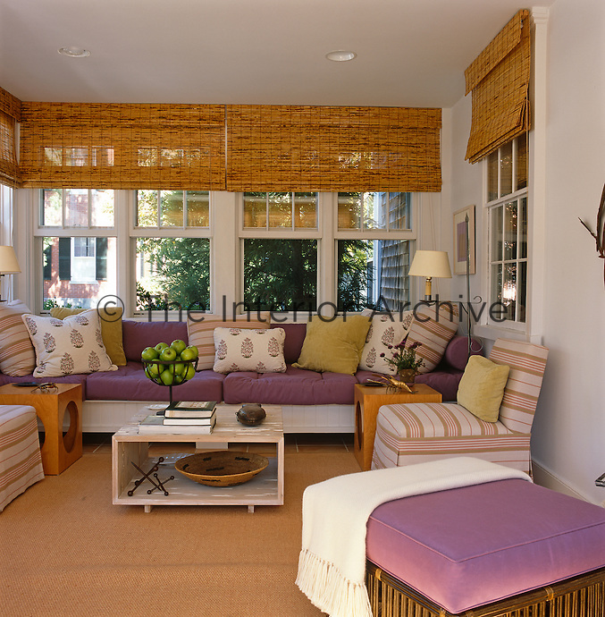 The sun room is a mixture of colour and pattern with built-in window seating and bamboo blinds