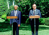 Washington, D.C. - June 25, 1990 -- United States President George H.W. Bush, right, welcomes Nelson Mandela, leader of the African National Congress (ANC) left, to the White House for talks on Monday, June 25, 1990.  This is Mandela's first visit to the United States following his release from Victor Verster Prison after 27 years in captivity..Credit: Ron Sachs / CNP
