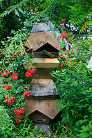 ,A hive of Ron Breland's design with his students. In 2000, after losing half his hives, Ron starting creating five-sided hives, for him closer to the natural habitat of bees.