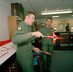 Two pilots the 'Red Arrows', Britain's Royal Air Force aerobatic team discuss finer points of aerobatic flying in crew room.