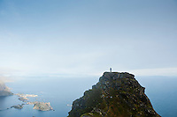 HIkier on isolated mountain peak with vestfjord in background, Reinebrinen, Lofoten Islands, Norway