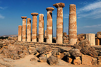 Low angle view of columns, Temple of Hercules, Agrigento, Sicily, Italy,  pictured on September 12, 2009, in the morning. The date of the Temple of Hercules is uncertain; although the style indicates late 6th century BC,  its entablature is mid 5th century. It was built with a peristasis of 6 x 15  tall Doric columns with wide capitals, and a cella with pronaos and opysthodomus, above a three-step basement.  8 columns and an altar have survived the earthquake which destroyed the temple. The Valley of the Temples is a UNESCO World Heritage Site. Picture by Manuel Cohen.