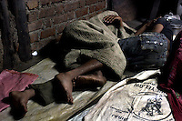 Waste plastic sorters sleep in the early morn. Many of Dharavi's residents dont have their own home and sleep on the floor of the room they work in. These migrant labourers are paid Rs80 ($1.80) a day, similar manual labour jobs outside Bombay would pay Rs60 a day.