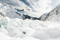 Helicopter hovering above crevassed up Franz Josef Glacier, Westland National Park, West Coast, New Zealand