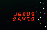 """""""Jesus Saves"""" neon sign in lit up at night in urban setting"""