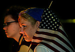 Candlelight bathes the faces of Justine Ryan and friend Nicole Reese, both of Milwaukie, as they attend vigil at Waterfront Park for terrorist attack victims Wednesday night. Justine smiles as people begin to talk of world peace and an end to hatred.