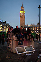 Protestors sit on a damaged bollard on Parliament Square in front of the Houses of Parliament during a student demonstration in Westminster, central London on the day the government passed a bill to increase university tuition fees.