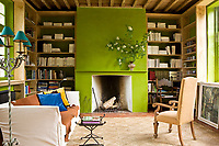 The chimney breast of the library is painted an eye-catching lime-green which brings the whole room to life