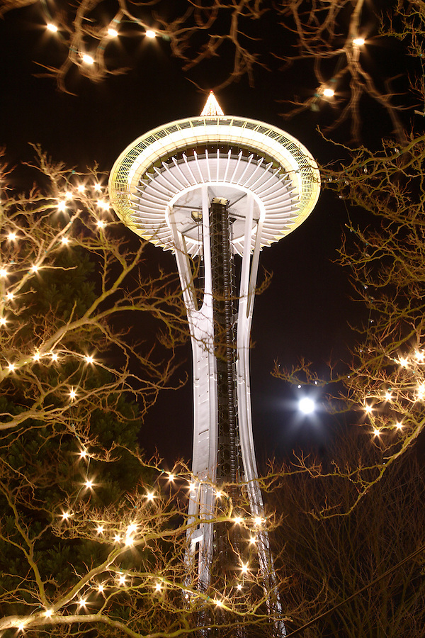 Nighttime scene of Seattle Space Needle and full moon through branches decorated with Christmas lights, Seattle Center, Seattle, Washington, USA