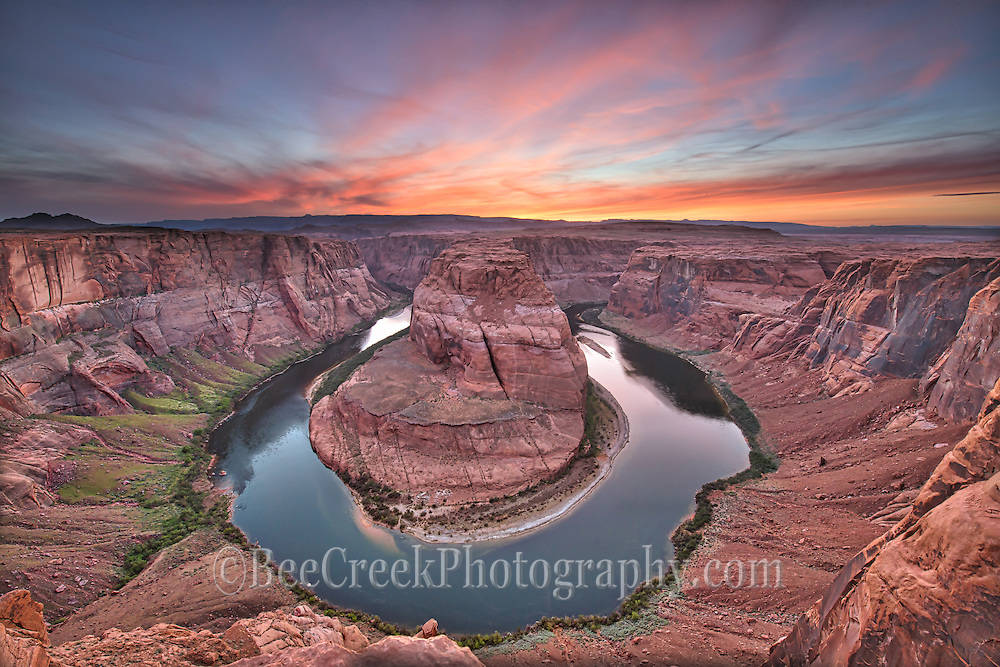 The Horshoe bend is a horseshoe-shaped meander of the Colorado River located near the town of Page, Arizona, in the United States. Horseshoe Bend is located 5 miles downstream from the Glen Canyon Dam and Lake Powell within Glen Canyon National Recreation Area, about 4 miles  southwest of Page. It is accessible via hiking a 1.5-mile  round trip from U.S. Route 89, but an access road also reaches the geological structure, as it is part of a state park. The Horseshoe Bend can be viewed from the steep cliff above. The overlook is 4,200 feet  above sea level and the Colorado River is at 3,200 feet above sea level, making it a 1,000-foot drop so watch your step.  The climb up does not taking any climbing but it is not a walk in the park.  I finally got to a spot for this photo and waited for the sun to set but it didn;t really do what I was hoping for so a lot of people left but I decided to stick around a little longer and I am glad I did because as the sun went down it lite up the sky with a array of colors from reds, pinks to oranges against a backdrop of blue for a spectacular sunset.