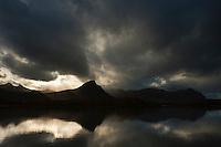 Reflection of mountain peak in Grasbukta, Lofoten Islands, Norway