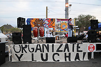 "Phoenix, Arizona. September 22, 2012 - ""Organize and Fight,"" is the message (written in Spanish language) on this large banner below a bandstand, on display at the ""Festival of Resistance"" rally organized to oppose the implementation of Arizona's SB 1070's law Section 2b. Photo by Eduardo Barraza © 2012"