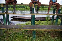 Men from the community take a breather after cutting the grass of the football field with machetes - Communidad Siete de Augosto - Amazonas - Colombia