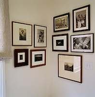 A collection of black and white photographs by Herb Ritts displayed on the walls in the corner of the bathroom