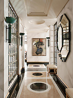 The hallway of a stylish apartment. Walls covered in marbleised hand painted paper and a polished floor creates an atmosphere where classic and modern elements coexist comfortably in a totally contemporary space.