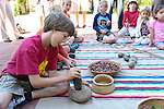 A young participant grinds cracked acorns in a stone pestle during acorn preparation.
