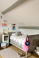 A painted French bed is the feature of this child's attic bedroom-.