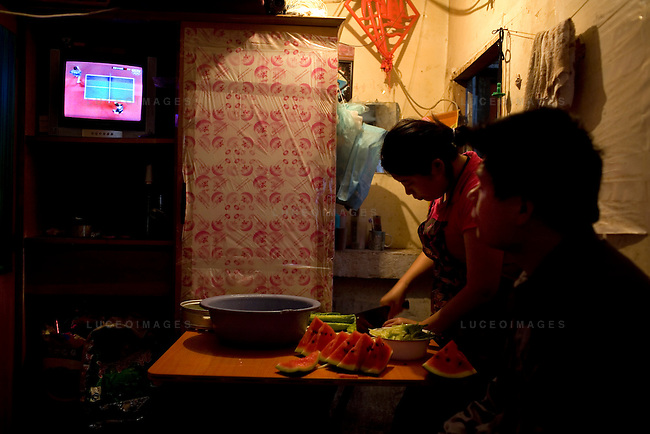 Sun Yu Bin and his wife Liu Guo Min watch an Olympic ping pong match from their bedroom, which also serves as their kitchen, in a hutong in Beijing, China on Friday, August 22, 2008.  Kevin German