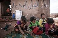 In this Sunday, Sep. 22, 2013 photo, Syrian internal displaced children sit outside an abandoned structure in a no man's land where their families have taken shelter after have fled from Kafr Nabudah village, their homeland turned into a battlefield where clashes between troops loyal to president Bashar Al-Assad and opposition fighters have broken out as many opposition armed groups launched a coordinated attack over the Syrian army positions in the Idlib province countryside, Syria. (Photo/AP).