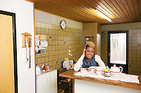 Switzerland. Canton Ticino. Aranno. Orpheline sits in her kitchen's home. Orpheline is a composer, song writer, a singer and a musician. She is a young woman (24 years old). Her mother is swiss and her father was a black american citizen. Mixed race. Aranno is located in the Malcantone area. 19.03.2010 © 2010 Didier Ruef