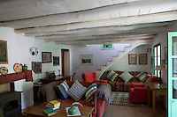 The cottage living room is simply furnished with comfortable sofas and plenty of cushions