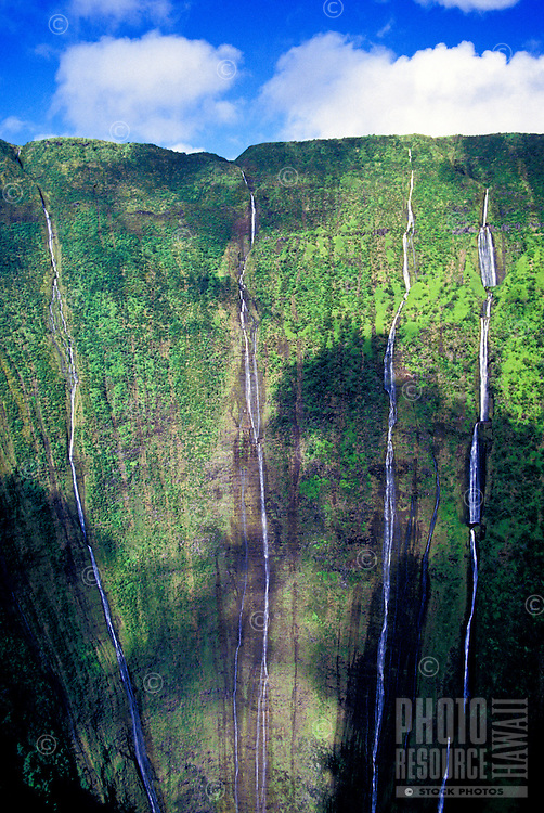 In Kohala on the Big Island, waterfalls flow down green mountains partly shaded by the shadows of clouds
