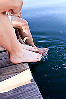 The bare legs and feet of three people sitting on a dock.