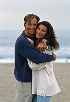 couple holding each other while on the beach in Santa Monica, CA