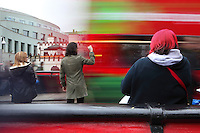 A tourist is taking pictures of Camden Town from the bridge after the passage of a multi-coloured bus, in the foreground a woman with red hair is waiting, London, UK. Picture by Manuel Cohen