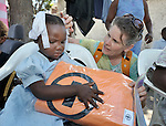 Anne Castleton (right), a consultant on disaster relief for Church World Service, a member of the ACT Alliance, delivers a blanket and hygiene kit to a young blind girl who survived Haiti's January 12 earthquake. She is part of a group of disabled Haitians who are receiving special attention from ACT Alliance members.