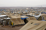 DOMIZ, IRAQ: A young Syrian refugee runs through the Domiz refugee camp in the Kurdish region of northern Iraq...The semi-autonomous region of Iraqi Kurdistan has accepted around 60,000 refugees from war-torn Syria. Around 20,000 refugees live in the Domiz camp which sits 60 km from the Iraq-Syria border...Photo by Younes Mohammad/Metrography