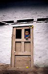 A young girl peeps out of the door of her home  high in the Himalayas in the Solly Khumbu region of the Himalayas, Nepal