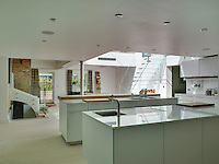 The large contemporary kitchen is accessed by a glass staircase