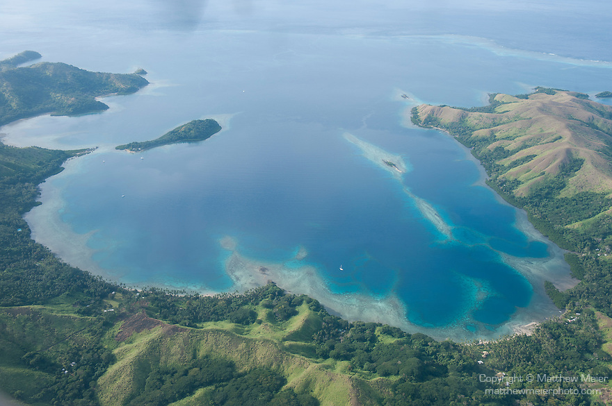 Vanua Levu, Fiji; aerial view of coral reefs lining a horseshoe shaped bay while flying from Viti Levu to Taveuni