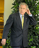 Washington, D.C. - July 2, 2008 -- United States President George W. Bush scratches his head as he walks from the Oval Office to make a statement on the upcoming 2008 G8 Summit in the Rose Garden of the White House on Wednesday, July 2, 2008.  In his remarks, the President said more U.S. troops may be needed for Afghanistan and urged Americans to pressure their congressman to lift the ban on off shore oil drilling..Credit: Ron Sachs / CNP