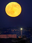 The full moon rising over Alcatraz Island in San Francisco, California.