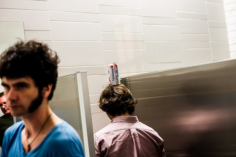 A Hopscotcher balances his beer while taking a bathroom break at CAM Thursday late night during the Thee Oh Sees performance.