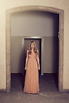 young woman standing straight at a door