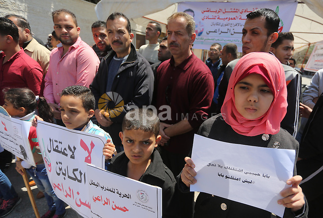 Palestinians hold banners during a protest in solidarity with the karate trainer, Hassan El-Raey against his arrest by the Israeli army, in front of Red cross office in Gaza city on April 13, 2016. Photo by Mohammed Asad