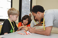 New York, NY, USA - June 23, 2012: William Ricci concentrates on his folding. Sipho Mabona teaches a class how to fold his original design, a complex origami bear. He helps young folders how to coordinate pre-creasing.