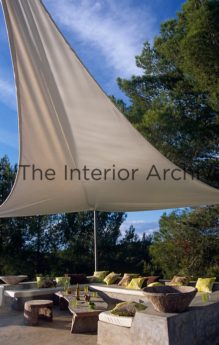 A sail-like awning provides shade over an outdoor seating area scattered with cushions