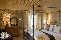 This charming bedroom has retained the original stone wall and is furnished with a contemporary four-poster bed