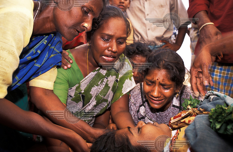 Distraught women grieving for a child killed by the tsunami which struck South Asia on 26/12/2004..An underwater earthquake measuring 9 on the Richter scale triggered a series of tidal waves which caused devastation when they struck dry land. 12 countries were affected by the tsunami, with a combined death toll of over 150,000.