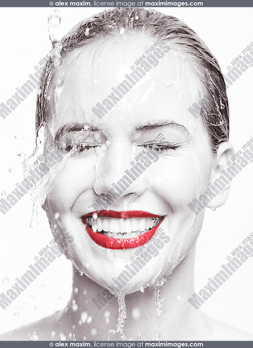 Artistic beauty portrait of a young smiling woman face with red lipstick with water running over it. Isolated on white background. Selective black and white.