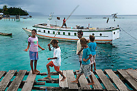 Raja Ampat Archipelago, West Papua, Indonesia, December 2010. Children are fishing on the jetty of Yembeser Village. Thousands of small islands fringed by coral reefs and blue water mangroves litter the Raja Ampat archipelago. The turquoise and blue waters are teeming with marine life that forms the livelihood for the local Papuan population. The Raja Ampat Research & Conservation Centre (RARCC) supports the locals to develop a community based, sustainable tourism project, inviting visitors to explore their islands by sea kayak and experience the culture by staying amongst the local people in traditional style homestays. Photo by Frits Meyst/Adventure4ever.com