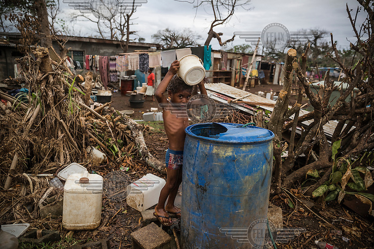Adam, 4, takes a bucket shower near his house, that was damaged by Cyclone Pam on 13 March 2015.