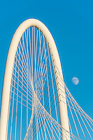 This is an image capture of the top of the Margaret Hill Hunt Bridge with a moon along side ot the bridge in downtowm Dallas.